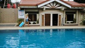 Louro em um chapéu, macacões com um saco azul, acordos da menina em um hotel tropical com uma piscina 4K vídeos de arquivo