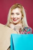 Louro emocional que guarda muitos sacos coloridos da compra Menina feliz com cabelo de Lond e sorriso encantador no rosa Fotografia de Stock Royalty Free