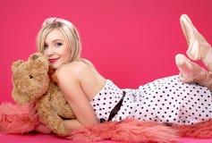 Louro encantador com o urso de peluche sobre a cor-de-rosa Imagens de Stock Royalty Free