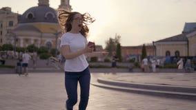 Louro engraçado que tem o divertimento na rua, uma dança da menina e rindo com um telefone em suas mãos 4K vídeos de arquivo