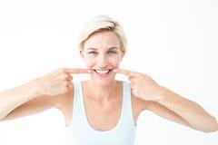 Louro feliz que sorri mostrando seu dente Foto de Stock