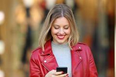 Louro feliz que usa um telefone esperto em uma alameda Imagens de Stock Royalty Free