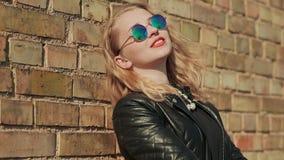 Louro novo à moda nos óculos de sol e no casaco de cabedal preto perto de uma parede de tijolo na rua filme