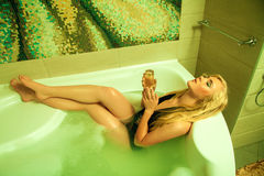 Louro novo atrativo no banho com vidro do champanhe Fotografia de Stock