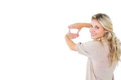 Louro novo atrativo que quadro com suas mãos Fotografia de Stock