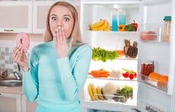 Louro novo em casa perto do refrigerador imagem de stock royalty free
