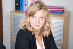 Louro ocasional feliz moderno da mulher de negócios com os olhos azuis que sentam-se em seu local de trabalho no escritório imagem de stock