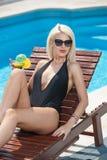 Louro sensual bonito com os óculos de sol elegantes que relaxam na piscina com um suco Mulher justa longa atrativa do cabelo Fotos de Stock Royalty Free