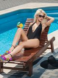 Louro sensual bonito com os óculos de sol elegantes que relaxam na piscina com um suco Mulher justa longa atrativa do cabelo Imagens de Stock Royalty Free
