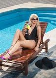 Louro sensual bonito com os óculos de sol elegantes que relaxam na piscina com um suco Mulher justa longa atrativa do cabelo Imagens de Stock