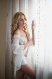 Louro 'sexy' atrativo com roupa interior branca do laço perto das cortinas que olham na janela. Retrato da mulher justa longa sens Imagens de Stock