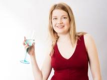 Louro 'sexy' no vestido vermelho e no vidro bebendo do vinho Imagens de Stock Royalty Free