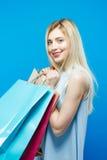 Louro surpreendente com cabelo de Lond e sorriso encantador no fundo azul no estúdio Mulher feliz que guarda muita compra Imagem de Stock