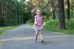 Louro três anos de menina idosa que corre no passeio do parque do asfalto Foto de Stock Royalty Free