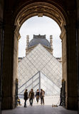 The Louvre Archway. Paris, France May 26 2015: Archway to the Louvre with tourists and hawkers selling souvenirs Royalty Free Stock Photography