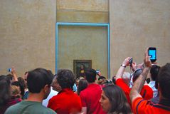 Louvre Art Museum Mona Lisa Crowd. Crowds are so deep around the Mona Lisa painting in  Paris Louvre museum that the best you can hope for is photo with camera Royalty Free Stock Images
