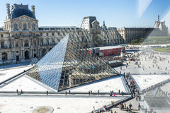 Louvre. The entrance to the Louvre museum in Paris through the glass pyramid with people queuing Royalty Free Stock Image
