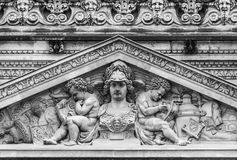 Louvre facade statue. Above the Passage Richelieu, as seen with a telephoto lens from the othe side of the PLace du Palais Royal - photograph taken in black and Royalty Free Stock Image