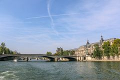 Louvre Museum and Carrousel Bridge with Blue Sky. Carrousel Bridge across the Seine River and Louvre Museum Stock Photo