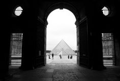 Louvre museum. Pyramid of glass. A black and white photograph of the famous in Paris, France, Europe.  Taken with framing effect from behind ancient stone arch Stock Photos