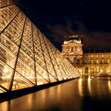 The Louvre museum at night in Paris Stock Photography