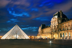 The Louvre museum at night in Paris Royalty Free Stock Photo