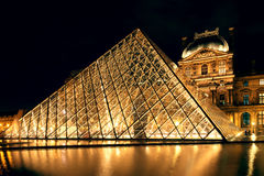 The Louvre museum at night in Paris Stock Photos