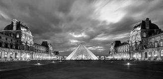 The Louvre museum at night in Paris Stock Image