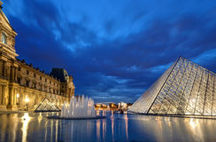 The Louvre museum at night in Paris Stock Photo