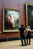 Louvre Museum, Paris. A young couple admires a romantic oil painting of a classical subject in the Louvre Royalty Free Stock Photos