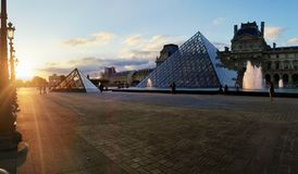 Louvre museum at sunset. The Louvre museum courtyard and the glass pyramids during the sunset Royalty Free Stock Photography