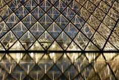 Louvre at night. Detail od the Louvre pyramids at night Stock Photos
