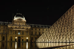Louvre by night. A beautiful double view in the water of Louvre by Night. Very quite and romantic Royalty Free Stock Image