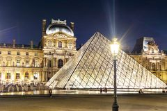 Louvre palace and pyramids at night, Paris, France stock photography