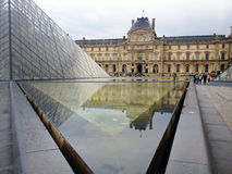 The Louvre. Paris,France - July 8th 2014: picture of part of the Louvre pyramid and the Louvre museum in background Royalty Free Stock Photos