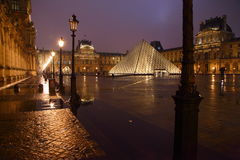 Louvre in Paris by night. Famous Louvre palace in rainy Paris by night Stock Photo