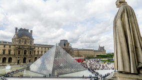 The Louvre, Paris with statue looking down. Paris, France May 28, 2015: The Louvre from high view point with statue looking down on the scene with many tourists stock images