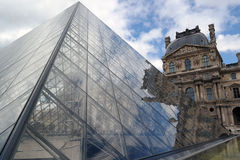Louvre Pyramid. Light reflections in the glass pyramids and water Royalty Free Stock Photo