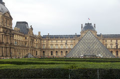 The Louvre pyramid. Paris,France - July 8th 2014: picture of the Louvre pyramid and the Louvre museum in background Royalty Free Stock Photo