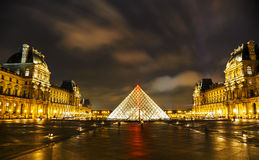 The Louvre Pyramid in Paris at night Stock Images