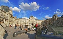 Louvre-Pyramide und Louvre-Palast drängten sich mit Touristen Lizenzfreie Stockfotografie