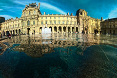 Louvre reflected in the water fountain in Paris Stock Photo