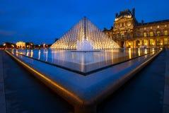 Louvremuseet på natten i Paris, Frankrike Fotografering för Bildbyråer