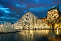 Louvremuseet på natten i Paris Royaltyfri Bild
