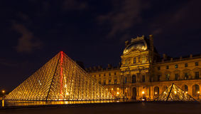 Louvremuseum och pyramiden i Paris, Frankrike, på nattillumien Royaltyfri Foto