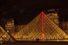 Louvremuseum och pyramiden i Paris, Frankrike, på nattillumien Fotografering för Bildbyråer
