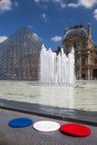 Louvrepyramid av museet och tre basker i färgerna av Royaltyfri Bild