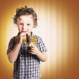 Lovable Little Child Eating Chocolate Easter Bunny. Present On Striped Brown Background Stock Photo