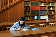LOVAINA, BÉLGICA - 5 DE SETEMBRO DE 2014: A menina nova desconhecida do estudante está sentando-se com o livro na biblioteca da u fotos de stock