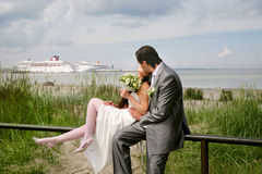 Love. A kissing wedding couple on a background of the sea and the ship Stock Photography